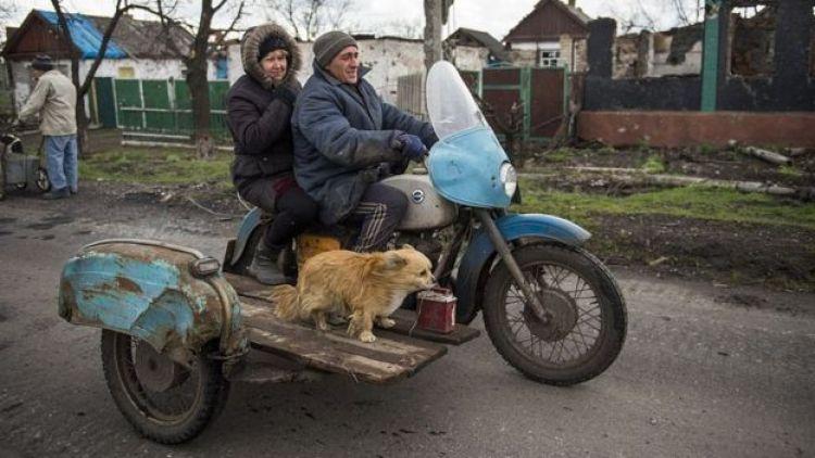 Пара на мотоциклі і пес