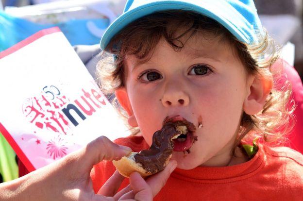 Un niño come un pedazo de pan con Nutella durante el aniversario 50 del producto.