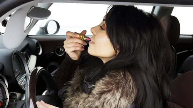 Driver applying make-up