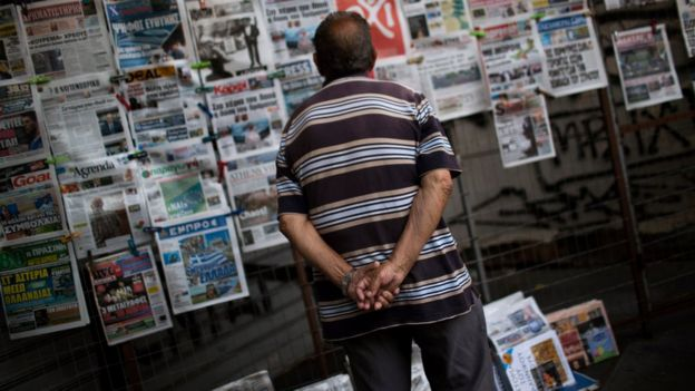 A man looking at newspapers