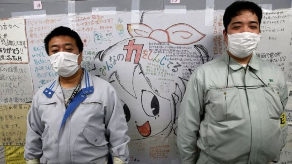 Two workers stand in front of a wall of messages of support