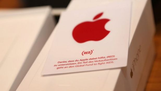 A sticker with the (RED) logo is seen on an iPhone box at the Apple Store on December 1, 2014 in Berlin, Germany