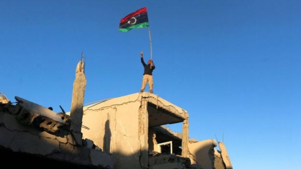 A fighter of Libyan forces allied with the U.N.-backed government waving a Libyan flag flashes victory sign as he stands atop the ruins of a house after forces finished clearing Ghiza Bahriya, the final district of the former Islamic State stronghold of Sirte, Libya