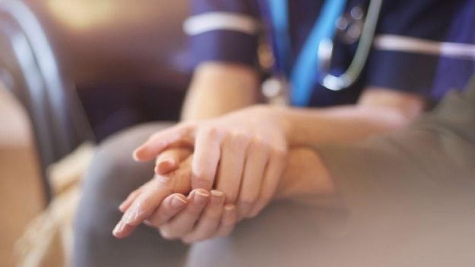 Enfermera tomándole la mano a un enfermo.