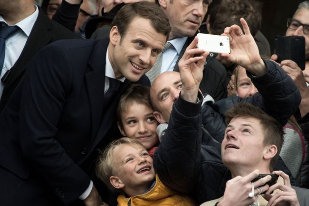 Supporters take photographs with the French President Emmanuel Macron