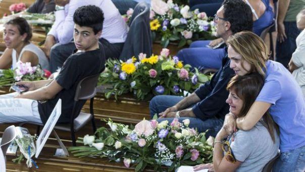 Mujeres llorando junto a los féretros de víctimas del terremoto