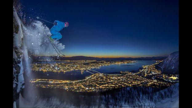 Hombre esquiando de noche