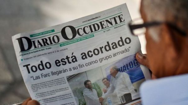 Un hombre lee un periódico anunciando el cierre de los acuerdos de paz en Colombia