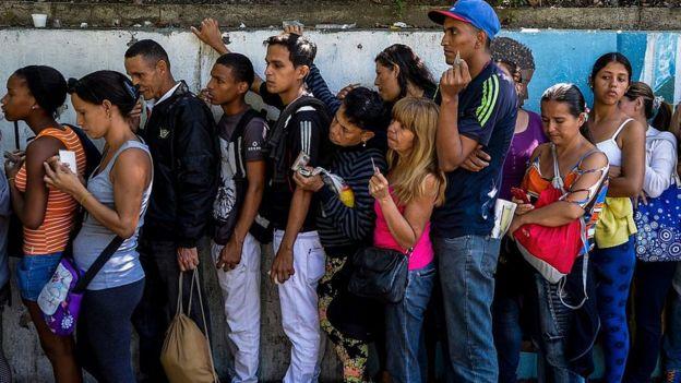 Venezolanos haciendo fila para comprar alimentos.