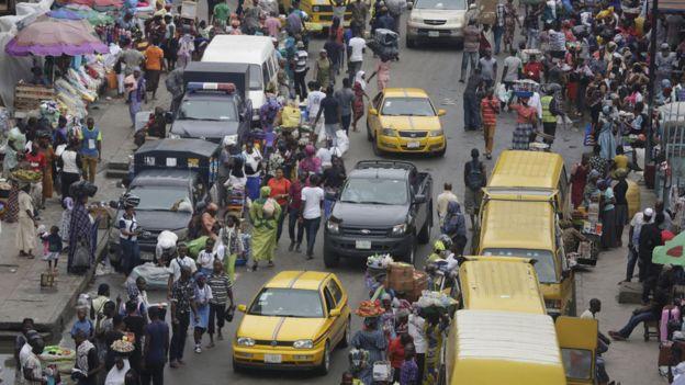 Pedestrians shop at a market in Lagos, Nigeria on 20 June 2016