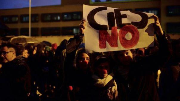 Protestas frente al centro de internamiento de extranjeros en Aluche, Madrid, con un cartel que reza