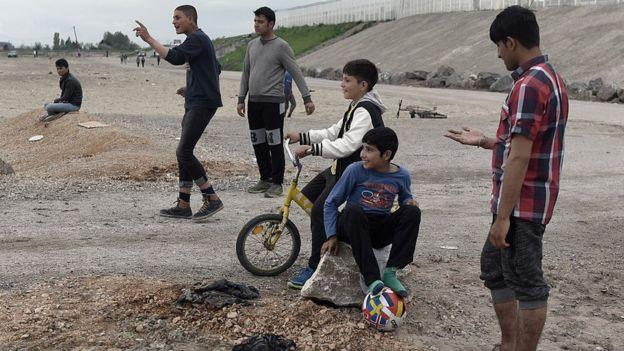 Jóvenes refugiados de Afganistán observan un juego de cricket en Calais, Francia.