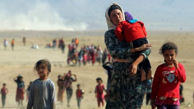 Displaced people from the minority Yazidi sect walk towards the Syrian border on the outskirts of Sinjar mountain on 11 August 2014.