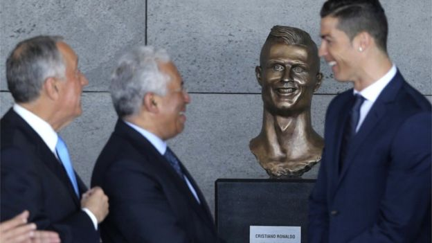 Ronaldo stands out of focus in front of his bust at the airport