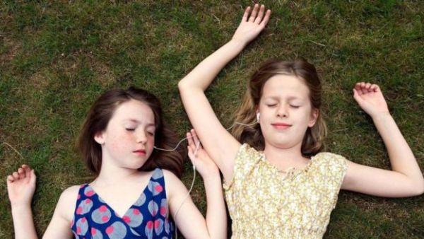 فتاتان تستمعان للموسيقى في أحد المتنزهات
