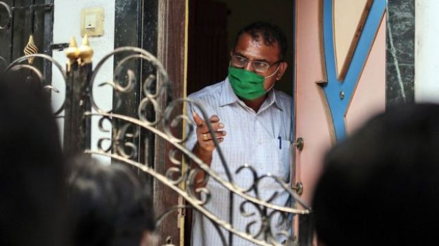 An Indian forensic expert looks from the door of a house in the Kasarvadavali area on the outskirt of Mumbai, India, 28 February 2016, where a 35-year-old man was suspected of murdering 14 family members before hanging himself