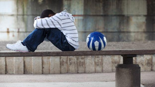 Chico en un banco con una pelota