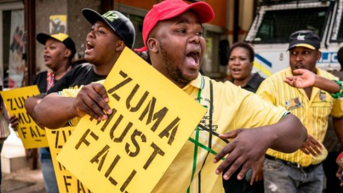 Supporters of the African National Congress Deputy President Cyril Ramaphosa hold placards and chant slogans outside the ANC party headquarter in Johannesburg, on February 5, 2018,