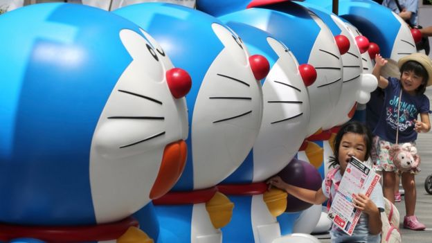 Girls touch models of Doraemon, a Japanese popular animation character, displayed at Tokyo's Roppongi Hills, 30 July 2016.