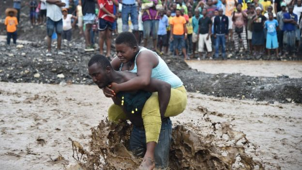 A man carries a woman across a river at Petit Goave where a bridge collapsed during the rains of Hurricane Matthew, south-west of Port-au-Prince, 5 October