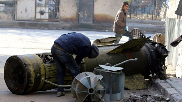 A man inspects an unexploded missile in the rebel-held Qaterji district of Aleppo (28 November 2016)