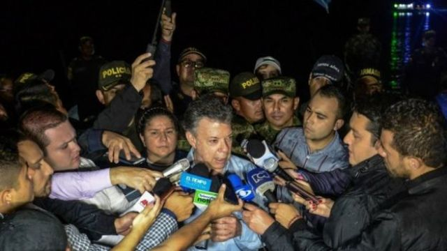 Colombian President Juan Manuel Santos (centre) answers questions from reporters