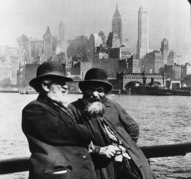 Two Jewish men lean against a barrier with the New York skyline behind them