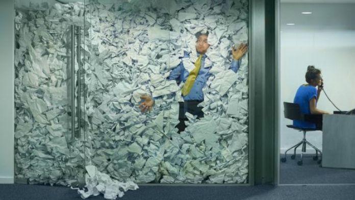 Hombre atrapado en un cubículo lleno de papeles