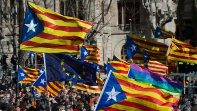 People hold Catalan pro-independence flags