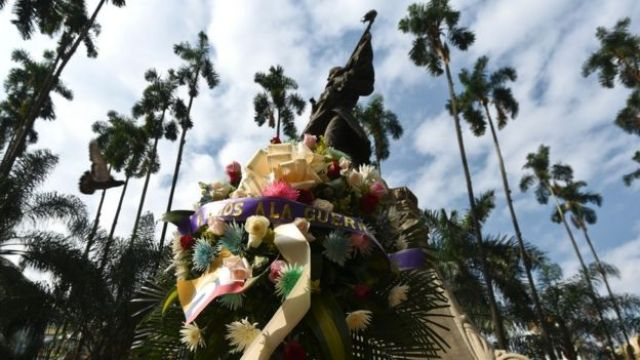 A wreath placed before the statue of one of the founding fathers of Colombia's independence, Joaquin de Cayzedo y Cuero at the main square in Cali, Colombia with a ribbon with an inscription that reads 'Farewell to War', on June 23, 2016