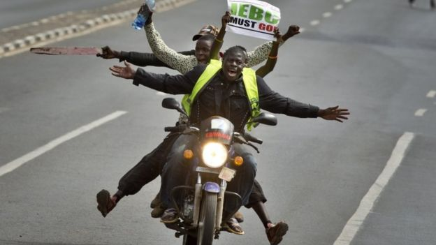 A motorcycle carrying protesters holding a placard using the acronym of the national electoral commission