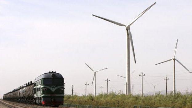 Un tren pasando al lado de turbinas de viento, en una planta de energía en Dabancheng, en la región de Xinjiang Uygur, en el noroeste de China