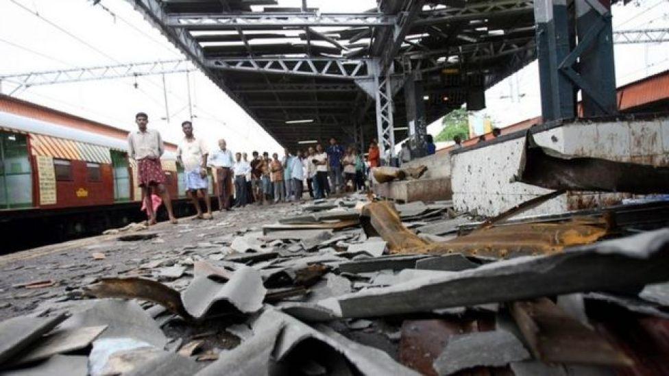 Commuters walk past the blast site at Mahim railway station in Mumbai 12 July 2006.