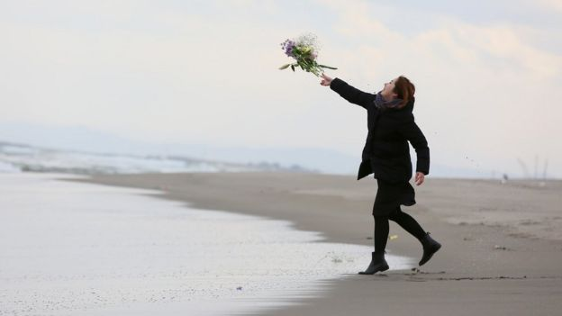 A woman throws a flower bunch at Fukanuma beach on March 11, 2016 in Sendai, Japan