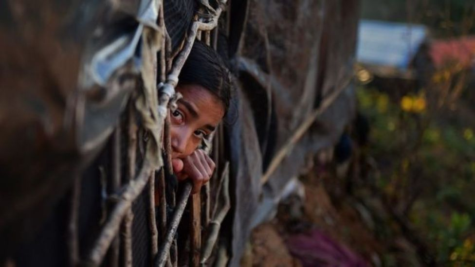 girl looking out from a makeshift shelter