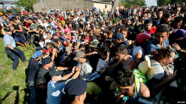 Migrants push policemen during a stampede to board buses in Tovarnik, Croatia September 17, 2015.