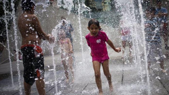 Una niña juega con el agua.