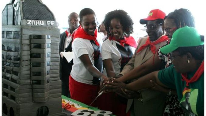 Zimbabwe's President Robert Mugabe (3rd R) cuts his birthday cake with the first family, his children Chatunga Mugabe (2nd L) and Bona Mugabe (C) and his wife Grace Mugabe (2nd R) during a 21st February Movement celebrations rally held in honor of his 89th birthday at Chipadze stadium in Bindura on March 2, 2013