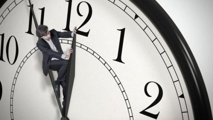 Hombre tratando de evitar que el reloj avance.