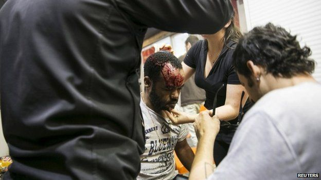 A protester, who is an Israeli Jews of Ethiopian origin, is treated for injury - Tel Aviv May 3, 2015