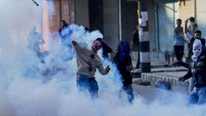 A Kashmiri masked Muslim protester throws back an exploded tear gas shell at Indian policemen during a protest in Srinagar, Indian controlled Kashmir, Tuesday, April 12, 2016.