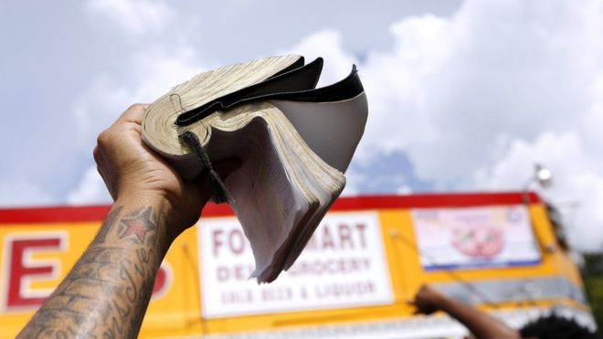 A demonstrator holds a bible at the Triple S convenience store where Alton Sterling was shot dead by police in Baton Rouge, Louisiana, U.S. July 9, 2016.