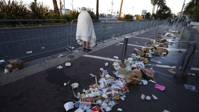 A man walks through debris on the street the day after a truck ran into a crowd