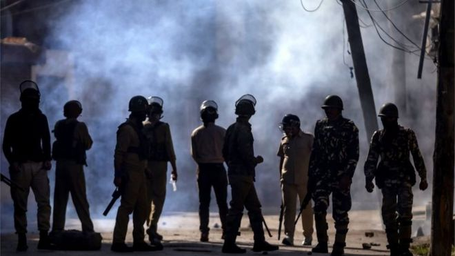 Indian paramilitary soldiers and policemen engulfed in smoke watch from a distance as Kashmiri protesters throw stones and bricks at them during a protest in Srinagar, Indian controlled Kashmir, Friday, Oct. 7, 2016.