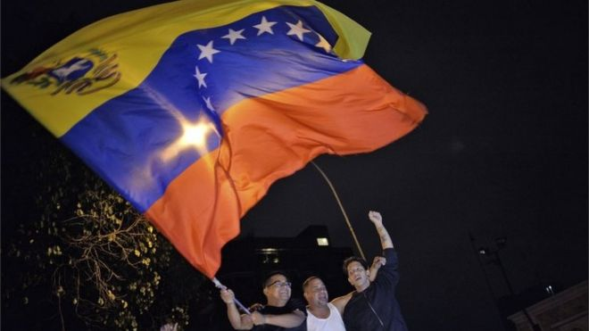 Venezuelan opposition supporters celebrate the results of the legislative election in Caracas on 7 December, 2015