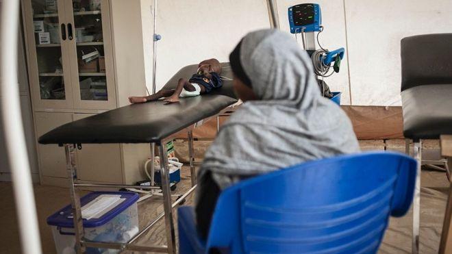 Menino com sua mãe em uma clínica de Maiduguri
