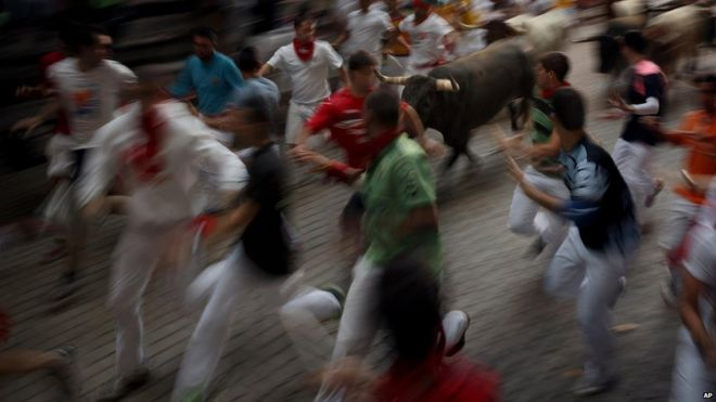 Revellers running with the bulls in Pamplona, Spain (14 July 2015)