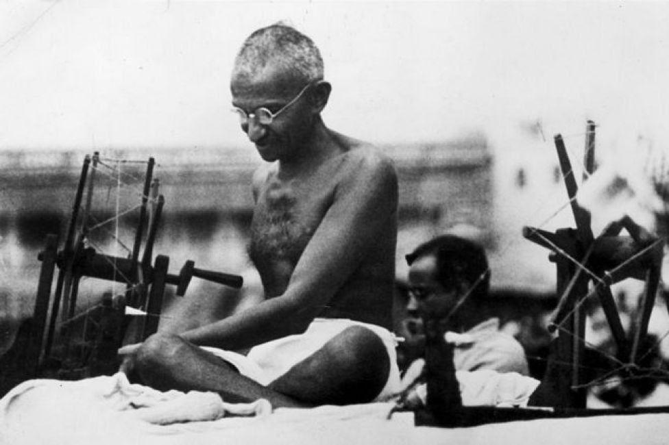 9th June 1925: Indian Nationalist leader Mahatma Gandhi (Mohandas Karamchand Gandhi, 1869 - 1948) at a spinning wheel during a 'Charlea' demonstration in Mirzapur, Uttar Pradesh.
