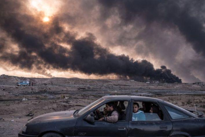 أسرة تفر من القتال في الموصل، وفي الخلفية تظهر حقول نفط القيارة وهي تحترق.