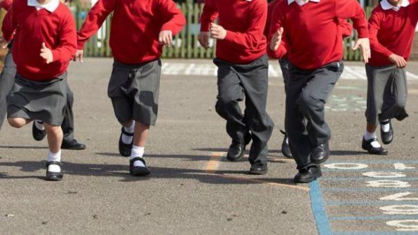 Niños no identificados corriendo en el patio de un colegio.
